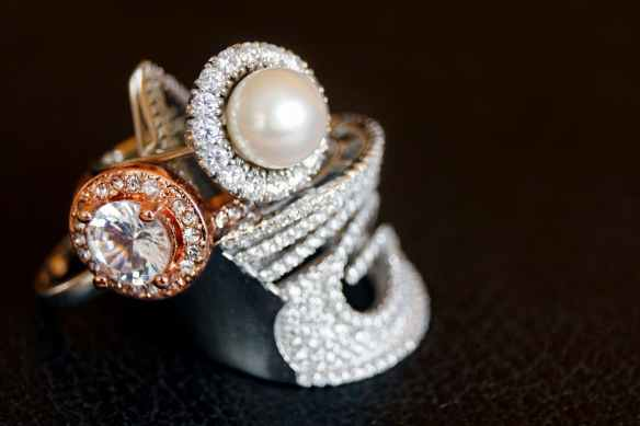 silver colored ring with clear gemstone and white pearl